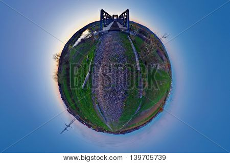 Stereographic (little planet) projection of a dismantled railway line with a bridge across the Mureș river after sunset near Târgu Mureș, Romania.
