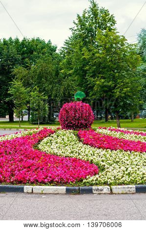 Summer park landscaping view - flowerbed with landscaping element in form of big apple covered with pink begonia flowers. Floral landscaping with begonia flowers in the summer park.