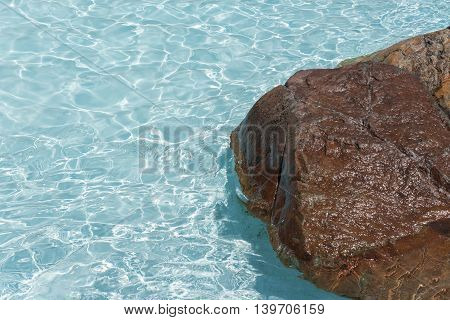 Relaxing Poolside image of Turquoise clear crystal water at a pool side with a large brown wet rock ideal set for background copy space texts blogs holiday ads and the web