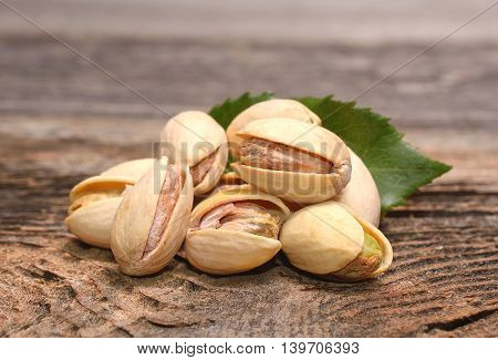 Roasted pistachios on wooden background in studio
