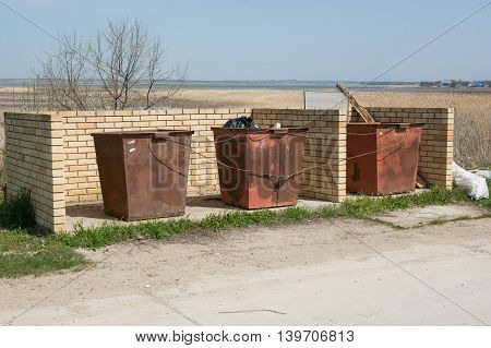 Three Garbage Tank Linked Metal Cable Are At The Designated Place And Enclosed By Brick