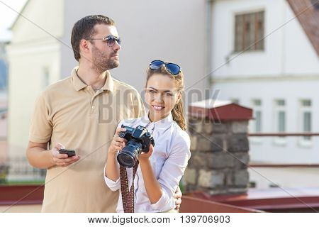 Travelling Concepts. Tourist Couple in Town Outdoors Taking PIctures Together. Happy Couple Vacation. Horizontal Image