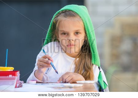 Thoughtful And Enthusiastic Girl Draws A Painting At The Table And Looked At The Frame
