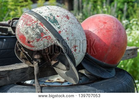 Old shabby motorcycle helmets. Obsolete helmets cracks belts mud red and white. The bursting of the coating.