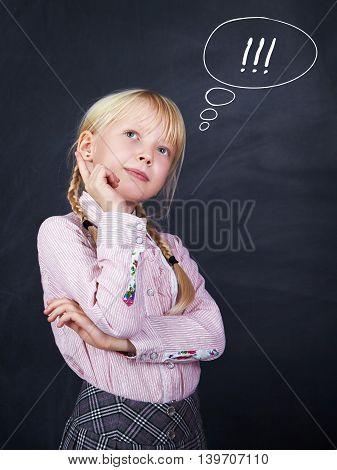 pensive schoolchild on the background of a blackboard. School and education