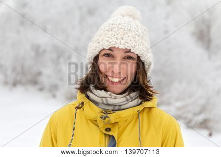 Girl in winter hat standing on a snowy street and smiles bright winter day snowy weather.