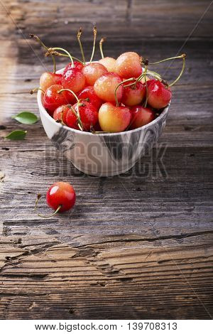 Ripe yellow cherries in a gray marble bowl on a wooden background. selective focus
