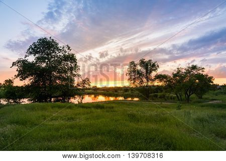 sunset on the lake, the beautiful sky in the reflection, green field in front