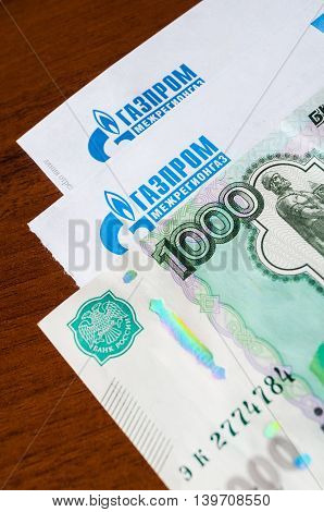 VELIKY NOVGOROD RUSSIA -JULY 24 2016. Letter with logo of Gazprom Mezhregiongaz and thousandths banknote on top. OO Gazprom Mezhregiongaz supplies natural gas to consumers in the Russian Federation.