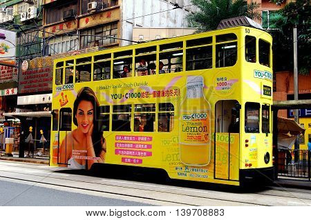 Hong Kong China - December 16 2007: A double-decker tram covered in advertising runs along its tracks on Des Voeux Road at Central *