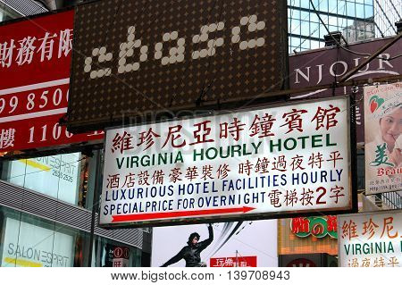 Hong Kong China - December 14 2005: Virginia Hourly Hotel sign and other business hanging signs on Sai Yeung Choi Street in Kowloon's Mong Kok commercial district