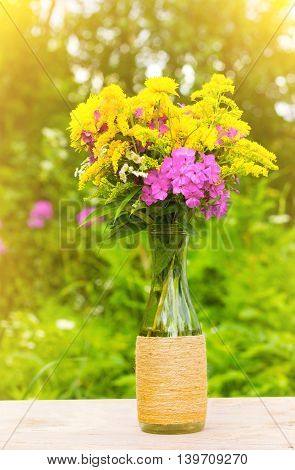 a bouquet of flowers of goldenrod phlox and lilies in a glass bottle on natural background in the golden rays of the sun