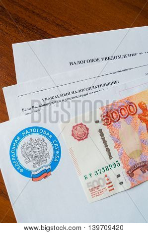 VELIKY NOVGOROD RUSSIA -JULY 24 2016. Tax payment notice letter with logo of Federal Tax Service of the Russian Federation and five thousand ruble banknote above. Tax payment concept.
