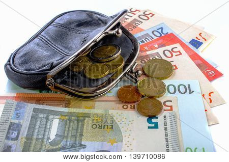 Euros in black purse and coins on a white background. Close-up.