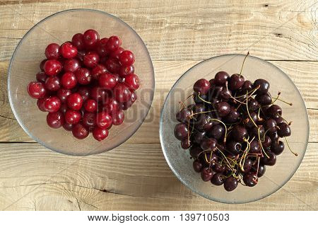 Cherries with water drops in glass bowl on dark wooden table top view