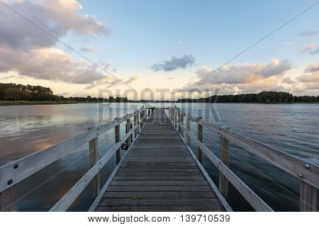 Wooden Jetty At Tranquil Lake During Sunset