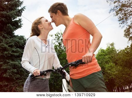 Happy couple in love during a bicycle ride outdoors at summer