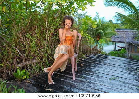 Photo young girl enjoying tropical fruits in jungle house. Smiling woman spending chill time outdoor summer. Horizontal picture