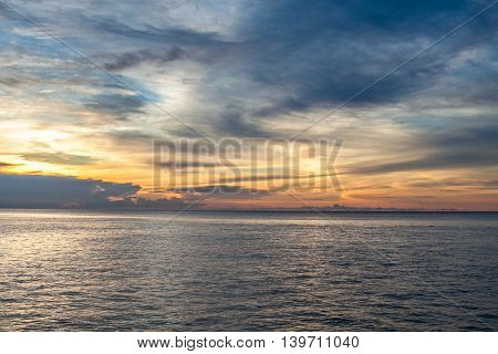 Photo of tropical sky at sunset.Seascape. Sun in the clouds over the sea. Horizontal picture