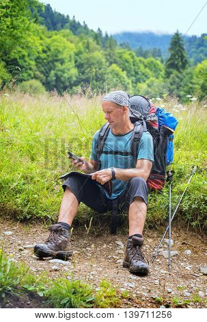 Hiking in the Carpathian mountains. Backpacker checks the route map and navigator sitting on the forest meadow