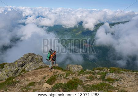 Tired hiker goes to the top rising up above the clouds. Heavy trekking in Carpathian Mountains