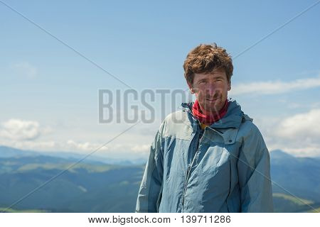 Portrait of a hiker on top against a background of distant hills. Blue Carpathian Mountains.