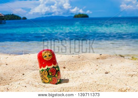 Photo Russian Handmade Dolls Matrioshka Untouched Tropical Beach in Bali Island. Horizontal Picture. Blurred Background. Closeup