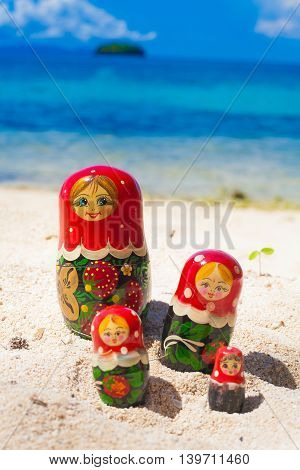 Photo Rows Puzzle Russian Dolls Matrioshka Family Souvenir Untouched Tropical Beach in Bali Island. Vertical Picture. Blurred Background. Closeup