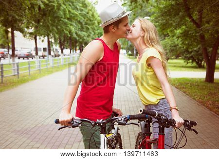 Happy couple kissing during a bicycle ride outdoors at summer