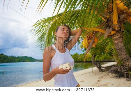 Photo young girl relaxing on beach with flowers at sunset. Smiling woman spending chill time outdoor Bali island. Summer Season Caribbean Ocean. Horizontal picture