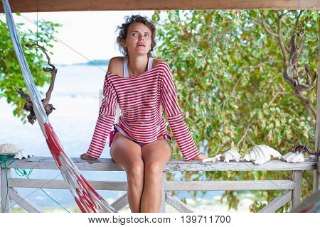 Photo young girl relaxing on beach in Bungalow. Smiling woman spending chill time outdoor summer. Caribbean Ocean Vacations. Horizontal, blurred background
