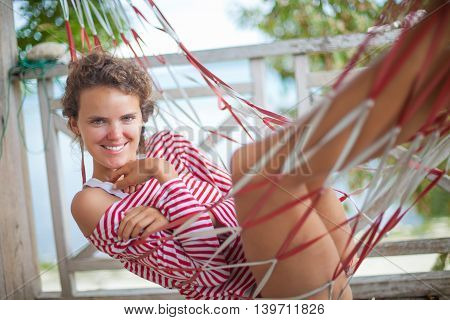 Portrait young sexy girl relaxing on beach Bungalow in hammock. Smiling woman spending chill time outdoor summer. Caribbean Ocean Vacations. Horizontal, blurred background