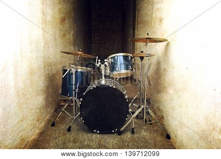 Drums conceptual image. Drum set percussion and cymbals in the dark corridor. Retro vintage grunge picture.