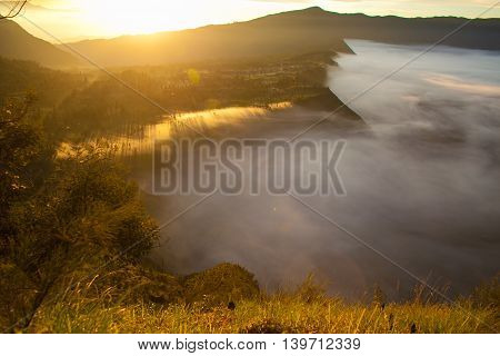 Sunrise Mountains.Asia Nature Morning Volcano Viewpoint.Mountain Trekking, View Landscape Valley Bali Village. Nobody photo. Horizontal picture. The first rays of the rising sun. White Fog