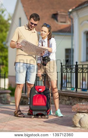 Travel and Vacation Concepts and Ideas. Happy Young Couple Sightseeing Places With Map. Vertical Image Composition