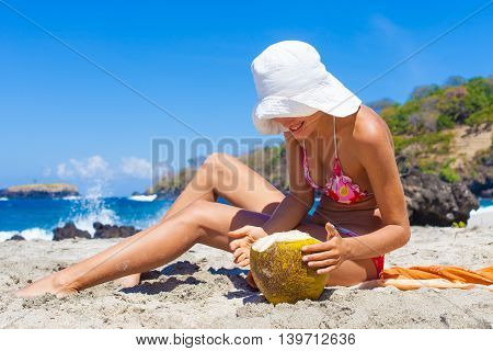 Photo young girl relaxing on beach with coconut. Smiling woman spending chill time outdoor summer. Horizontal picture