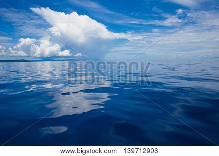 Photo of Blue Sea and Tropical Sky Clouds. Seascape. Sun over Water, Sunrise. Horizontal. Nobody Picture. Ocean Background