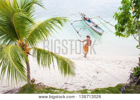 Photo Natural Wood Long Tail Boat Parked Caribbean Ocean Beach Island. Clear Blue Water Green Palm and Young Girl Dancing Background. Horizontal