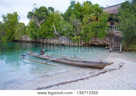 Photo Natural Wood Long Tail Boat Parked Caribbean Ocean Island Pier. Clear blue water. Horizontal image. Beautiful View background