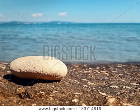 Closeup of pebble rock at the beach near the water. Journey summer vacation concept