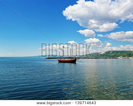 Sail boat floating in the sea near the pear at Balchik city Bulgaria. Summer vacation background. Joy happiness and recreation concept