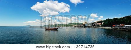 Clear morning panoramic view with a sail boat floating in the Black Sea Balchik city Bulgaria. Summer vacation background. Joy happiness and recreation concept