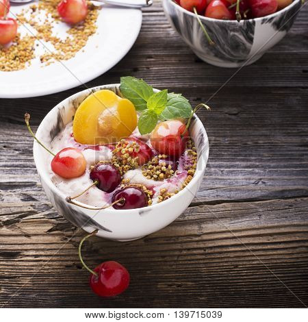 Healthy breakfast snack. Marble Portion bowl full of cherry smoothie with natural yogurt, ripe berries, fruits, bee pollen, berry syrup on a wooden background. selective focus