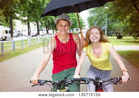 Happy young couple riding a bicycle in the rain