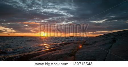 Orange and gray evening seascape. Lake Onega Waves beat against the stone shore which reflects the rays of the setting sun on the background of a dramatic stormy sky.