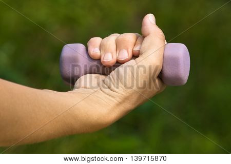 hand doing exercises with dumbbell on nature background