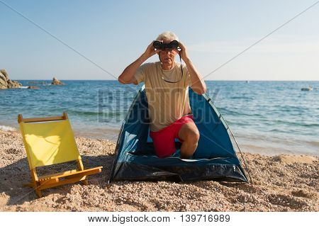 Man with spy glasses camping at the beach