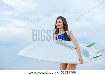 Smiling happy girl  holding surf board