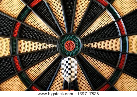 Dart arrow hitting in the target on dartboard