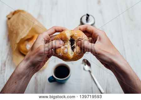Man Hands Eating Bismarck Donut With Coffee On Wooden Table